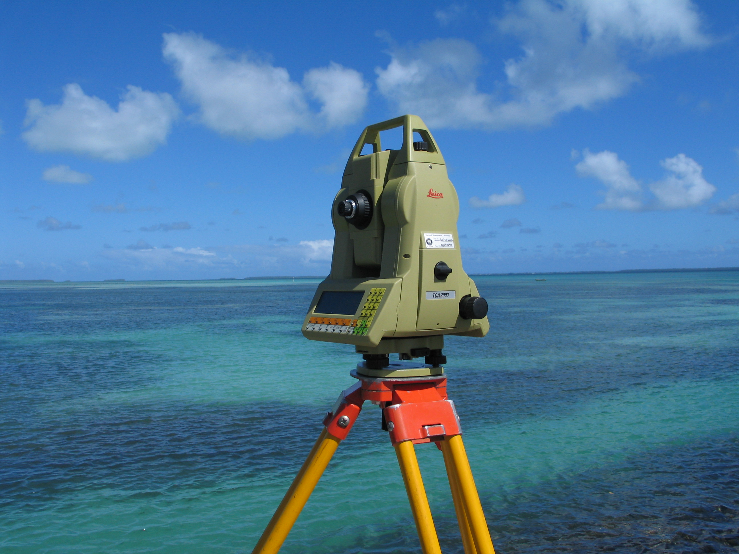 Picture of a modern day total station Theodolite machine, lookng out over an ocean view.
