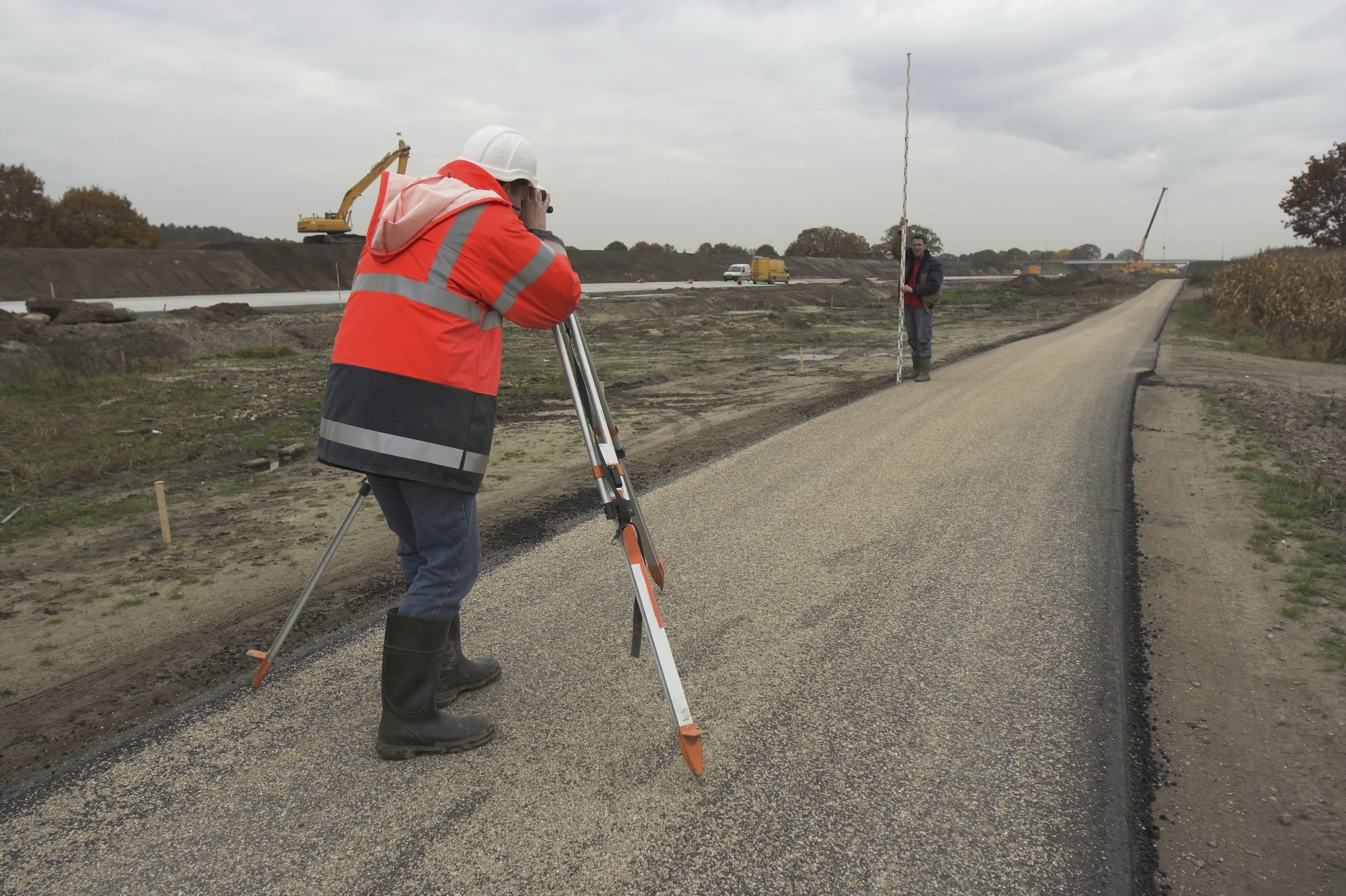 Image of a surveyor at work using an optical levelling instrument